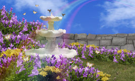 Water Fountain Garden. A water fountain in garden filled with purple and yellow flowers and bordered by stone wall. Hummingbirds at fountain, ladybugs in stock photo