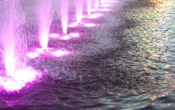 Magenta color lights and Water fountain jets. Water fountain magenta color lights detail stock image