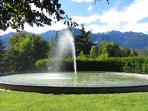 Water fountain with mountain background in a bright sunny day Royalty Free Stock Photos
