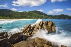 Water fountain over granite rocks,wild tropical beach with palms Stock Photo