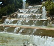 Water Fountain over stone steps. A water fountain in Barcelona over stone steps with grasses and sunshine Stock Photo