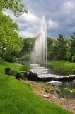 Water Fountain on Pond. Water fountain surrounded by lush green gardens and rocks Stock Image