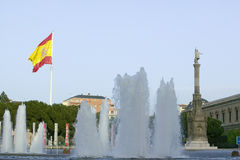 Water fountain and Spanish flag waves behind statue of Christopher Columbus at Plaza de Col�n in Madrid, Spain Royalty Free Stock Image