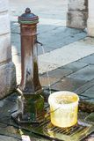 A Water Fountain. Venice, Italy - February 28, 2015: A public water fountain pours a continuous stream of water filling a bucket left nearby in the sun on a royalty free stock images
