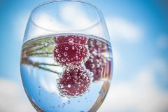 Water with fresh fruits and glass dishware.cocktails with ripe sweet red cherry on blue sky background. Lemonade, summer. Summer drink with sweet cherry. Copy Stock Photo