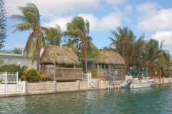 Water front Tiki Huts. Waterfront home with tiki huts with palm trees stock photography