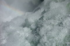 Water frothing from a waterfall with a faint rainbow. Stock Images