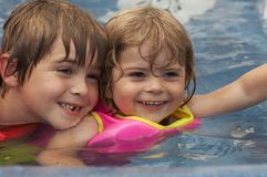 Water fun. Young pretty girl and boy smiling in water stock photography