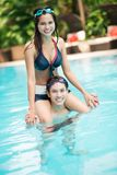 Water fun. Vertical shot of a young couple having fun in a swimming pool Stock Images