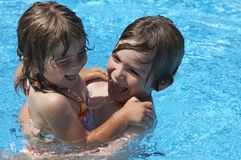 Water fun. A brother and sister playing in a pool stock image