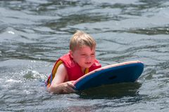Water fun. Young boy playing in water on boogie board Stock Photos