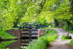 Water gates on Bansigstoke Canal in Woking, Surrey. Water gates on Bansigstoke Canal at walkpath in Goldsworth Park near St John village in Woking, Surrey Royalty Free Stock Photography