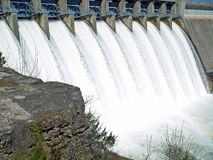 Water gates open. Water pouring over flood gates of a dam Stock Photos