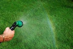 Water geven, die tot een raindow leidt Stock Foto