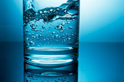 Water in glass. Pouring water in glass bottom closeup in blue light Stock Photos