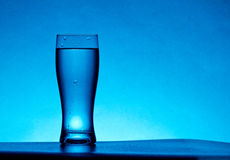 Water Glass. A blue water glass on studio background Royalty Free Stock Images