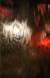 Water On Glass. Water coursing down a thick glass sheet with red and white lights in background royalty free stock photos