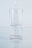 Water Glass. Glass of water over a light blue background stock photography