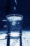 Water glass filling. Water glass being filled on dark background with drops Royalty Free Stock Images