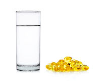 Water of glass with fish oil capsules isolated on the white back Royalty Free Stock Image