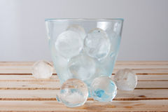 Water glass full of ice balls on a wood Stock Photo