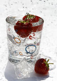 Water glass ice cube and strawberries Royalty Free Stock Image