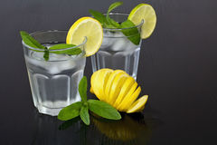 Water in a glass of ice cubes, lemon and fresh mint. Water cup for solid health. Drops of water on the cups. Stock Photos