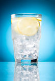 Water glass with lemon and ice isolated on blue Royalty Free Stock Images