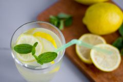 Water in a glass with lemon and oregano leaves,a refreshing soft drink to quench your thirst in the heat and maintain tone. / royalty free stock image