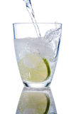 Water glass and lime. A glass of fresh drinking water and a lime. mineral water as a thirst quencher Stock Image
