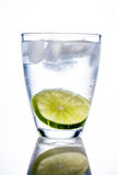Water glass and lime. A glass of fresh drinking water and a lime. bottled water as a thirst quencher Royalty Free Stock Images
