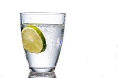 Water glass and lime. A glass of fresh drinking water and a lime. mineral water as a thirst quencher Stock Photography