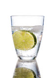 Water glass and lime. A glass of fresh drinking water and a lime. mineral water as a thirst quencher Royalty Free Stock Image