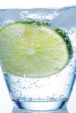 Water glass and lime. A glass of fresh drinking water and a lime. mineral water as a thirst quencher Stock Photo