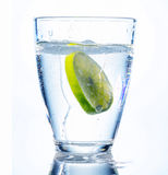 Water glass and lime. A glass of fresh drinking water and a lime. mineral water as a thirst quencher Royalty Free Stock Photo