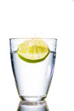 Water glass and lime. A glass of fresh drinking water and a lime. mineral water as a thirst quencher Royalty Free Stock Photos
