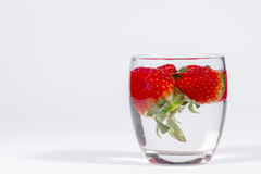 Water glass with several floating strawberries, blank space at left Stock Photography