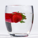 Water glass with several floating strawberries Royalty Free Stock Photography