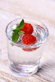 Water in glass with two raspberries and mint Stock Image