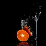 Water in glass with water splash with tangerine energy Royalty Free Stock Images