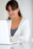 Water glass and woman working on laptop. Water glass on a work desk and a young woman working on laptop on blur background Stock Images