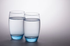 Water Glasses. Two transparent blue tinted water glasses overlapping on white to gray concentric background royalty free stock photography