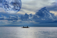 Water, global source of life. Blue gloomy sunset on a tropical sea with a cloudscape and globe, and fishermen in a small boat leaving for the nightly catch Royalty Free Stock Photo