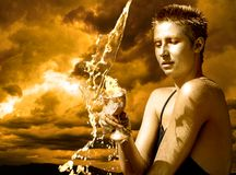 Water Goddess. Young woman holding a cup under pouring water against stormy skies Royalty Free Stock Photo