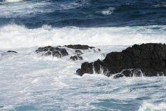 Water, golven die over rotsen verpletteren Stock Foto's