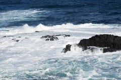 Water, golven die over rotsen verpletteren Stock Afbeeldingen