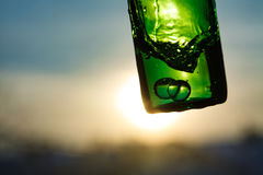 Water in green bottle with bubbles. Splashes of water in green glass bottle with bubbles and backlight Stock Photography