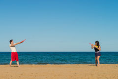 Water gun fight. Couple having fun on the beach with a water gun fight royalty free stock photos