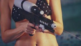 Water gun shooting splash in slow motion. Water gun in woman hands stock footage