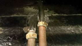 Water gushing from two copper overflow pipes into a gully stock video